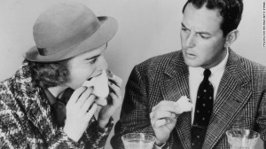 A man expresses disapproval at his friend's table manners as she sinks her teeth greedily into a sandwich, circa 1940.