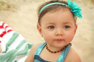 Maisie wearing a custom made headband, Art of Cure raw amber teething necklace, and 14kt gold and diamond earrings