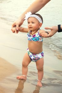 Maisie in a Hanna Andersson bikini, Art of Cure teething necklace, and her Saffron Bells silver baby anklets